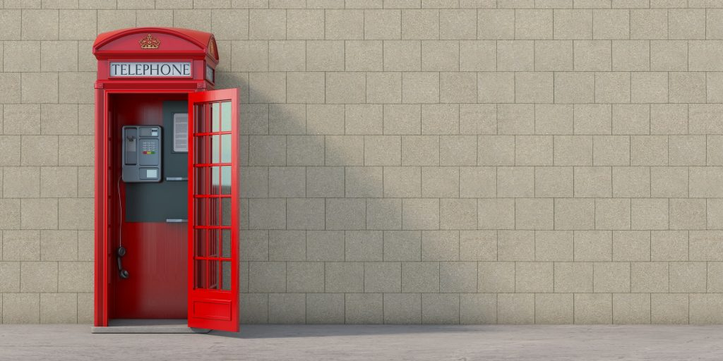 Red phone booth with hanging receiver on wall background. London